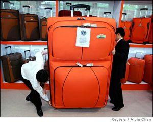 Staff members try to move a huge trolley case during the 100th Chinese Export Commodities Fair in Guangzhou, south China's Guangdong province October 15, 2006. This trolley case has been certified as the world's largest by the Guinness World Records and measures 175cm (5ft 9in) by 115cm (3ft 9.3in) by 46cm (1ft 6.1in) thick. Picture taken October 15, 2006. CHINA OUT REUTERS/Alvin Chan (CHINA)